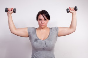 Size plus woman sweating during weight training